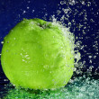 Whole green apple with stopped motion water drops on deep blue - Stockfoto