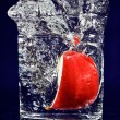 Slice of red apple falling down in glass with water on deep blue - Stockfoto