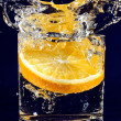 Slice of orange falling down in glass with water on deep blue — 图库照片