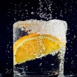 Stock Photo: Slice of orange falling down in glass with water on deep blue