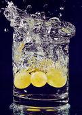 Hrozen bílých padají ve sklenici s vodou na hluboké b — Stock fotografie