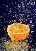 La mitad de naranja con agua movimiento detenido cae sobre el azul profundo — Foto de Stock