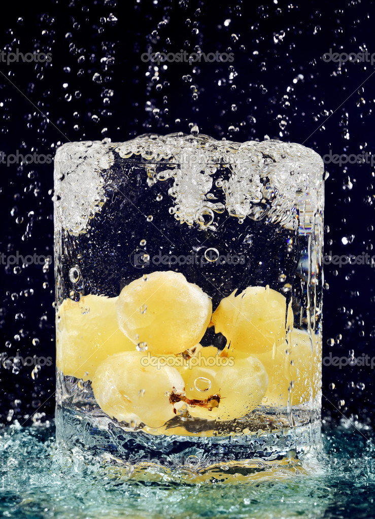 Bunch of white grapes falling down in glass with water on deep blue — Stock Photo #4003835