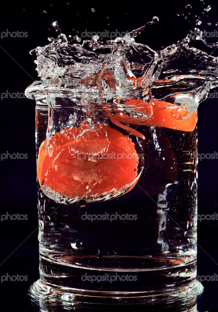 Red tomato falling down in glass with water on deep blue  Stock Photo #4003838