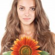 Stock Photo: Young beautiful womwith long hairs holding sunflower near fac