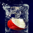 Slice of red apple falling down in glass with water on deep blue — ストック写真