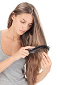 Young brunette beautiful lady combing long hairs on white — Stock Photo