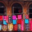 Storefront of old nepal textile shop with many multicolored garm - Stock Photo