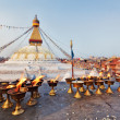 Many sacred candles in front of Boudha Nath (Bodhnath) stupa in - Stock Photo