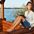 Stock Photo: Young pensive lady with book in summerhouse on sunset