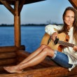 Young woman playing guitar in summerhouse on sunset — Stock Photo