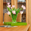 Stock Photo: Bouquet of pink tulips flowers in glass vase on wooden table
