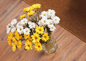 Bouquet of chamomile flowers in glass vase on wooden floor — Stock Photo