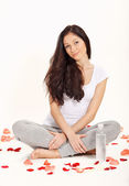 Young beautiful woman sitting in lotus pose with bottle of water — Stock Photo