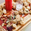 Still life with red candle and dried rose flowers on a gold tray — Stock Photo
