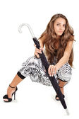 Young pretty lady in harem pants posing with black umbrella on w — Stock Photo