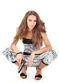 Young woman in harem pants posing with black pistol on white — Stock Photo