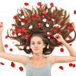 Young beautiful brunette woman with scattered long hairs and ros — Stock Photo