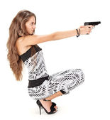 Young woman in harem pants aiming with black pistol on white — Stock Photo