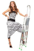 Young woman in harem pants posing with step-ladder on white — Stock Photo