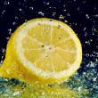 Half of lemon with stopped motion water drops on black - Stock Photo