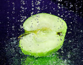 Half of green apple with stopped motion water drops on deep blue — Stock Photo