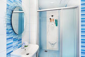 Modern blue bathroom interior with round mirror and shower cubic — Stock Photo