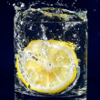 Half of lemon falling down in glass with water on deep blue — Stock Photo