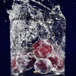 Bunch of red grapes falling down in glass with water on deep blu - Foto de Stock  