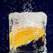 Slice of orange falling down in glass with water on deep blue - Stock Photo