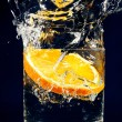 Slice of orange falling down in glass with water on deep blue - Stockfoto