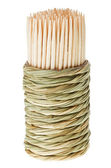 Bunch of wooden toothpick in round wattled straw holder — Stock Photo