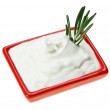 Stock Photo: Sour cream in red small square plate with rosemary twig