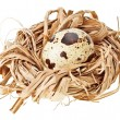 One quail eggs in the straw nest - Stock Photo