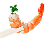 Cooked tiger shrimp with thyme twig in chopsticks — Stock Photo
