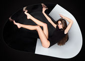 Young slim beautiful lady dressed in black slinky combi dress in — Stock Photo
