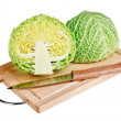 Fresh green cabbage with knife on wooden chopping board over whi — Stock Photo