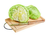 Fresh green iceberg lettuce with knife on wooden chopping board — Stock Photo