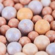 Beige cosmetics multicolor rouge balls background, macro view - Stockfoto