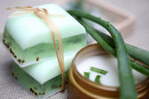Handmade soap bars, aloe, vera leaves and moisturizer. — Stock Photo