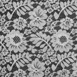 White fine lace floral texture on black background — Stock Photo