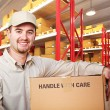 Delivery man in warehouse — Stock Photo