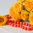 Yellow roses and coral beads — Stock Photo