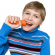 Teen eats carrots. He has strong teeth. — Stock Photo