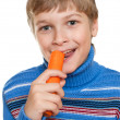 Royalty-Free Stock Photo: Teen eats carrots. He has strong teeth.