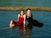 Girls in wet dress sits in water — Stock Photo