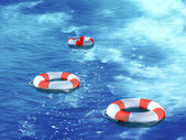 Three lifebuoys, floating on waves — Stock Photo