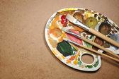 Dirty palette with paintbrushes on the cardboard paper — Stock Photo