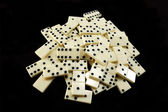 Stack of white dominoes on black background — Stock Photo