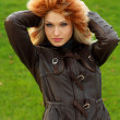 Foto Stock: Sexual blonde in brown leather jacket